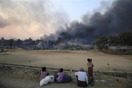 Smoke rises as people look on in Meikhtila, March 21, 2013. REUTERS-Soe Zeya Tun