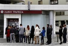 """Люди стоят в очереди к банкомату банка Laiki в Никосии, 21 марта 2013 года. Вторая попытка Кипра получить помощь, судя по всему, принесет в жертву держателей крупных вкладов. Политики, которые заблокировали закон о налоге на мелких вкладчиков, готовятся проголосовать за новую схему. Но, хотя перевод крупных депозитов Laiki - второго по величине банка Кипра - в """"плохой банк"""" выглядит более справедливым, этому плану грозит множество препятствий. REUTERS/Yannis Behrakis"""