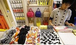 A clerk works at Kate Spade's new Saturday label store in Tokyo March 21, 2013. REUTERS/Toru Hanai