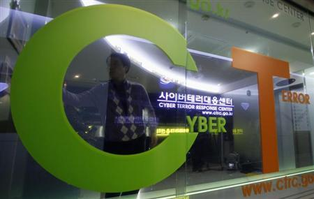 An investigator entering the Cyber Terror Response Center of the Korean National Police Agency is reflected on a window in Seoul March 21, 2013. REUTERS/Lee Jae-Won