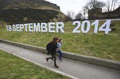 Учительница и ученица пробегают мимо знака, указывающего на дату проведения референдума о независимости Шотландии в Эдинбурге, 21 марта 2013 года. Население Шотландии проголосует 18 сентября 2014 года на референдуме, ответив на вопрос, хочет ли оно отделения от Великобритании после 300-летнего пребывания в составе единого королевства. REUTERS/David Moir