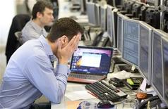 A trader reacts on the IG Group trading floor in London March 18, 2013. REUTERS/Neil Hall