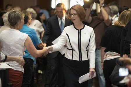 Australian Prime Minister Julia Gillard (C) greets members of the audience as Opposition leader Tony Abbott follows as she arrives to the National Apology for Forced Adoptions ceremony at Parliament House in Canberra March 21, 2013 in this picture provided by the Australian Attorney-General's Department. Gillard has apologised to victims of Australia's policy of forced adoption that saw as many as 150,000 babies of unmarried, mostly teenage mothers, taken by the state and given to childless married couples between the 1950s and the mid-1970s. Gillard told hundreds of people at a special ceremony in Canberra on Thursday, including those directly affected by the policy, that ''we acknowledge your loss and grief,'' and ''we apologise''. REUTERS/Penny Bradfield/Attorney-General's Department/Handout