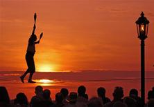 Busker Will Soto walks a tightrope at the sunset celebration in Key West, Florida, in this file photo taken in 2007. The sunset celebration at Mallory Square is a daily ritual for visitors to this subtropical island at the bottom of the Florida Keys. The Florida Keys are the end of the road, where the legendary U.S. Route 1 stops for the ocean at mile zero, a classic American road trip. REUTERS/Bob Krist/Florida Keys News Bureau/Handout