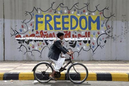 A boy rides past a graffiti on his bicycle in Sanaa April 13, 2012. REUTERS/Mohamed al-Sayaghi