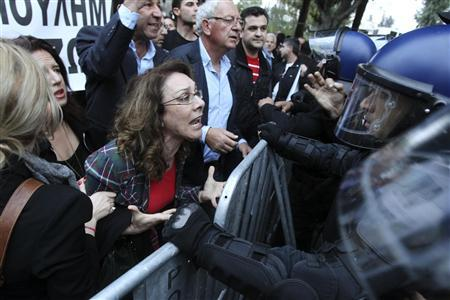 A protester yells at policemen during a protest by employees of Cyprus Popular Bank outside the parliament in Nicosia March 21, 2013. REUTERS/Andreas Manolis
