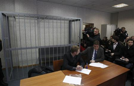 Attorneys of lawyer Sergei Magnitsky sit in front of an empty defendants' cage during a court session in Moscow March 22, 2013. REUTERS/Mikhail Voskresensky