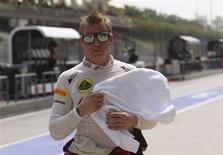 Piloto de fórmula 1, Kimi Raikkonen, caminha pelo pit após sessão de treino na Malásia. Raikkonen repetiu nesta sexta-feira o bom desempenho que o levou à vitória na primeira corrida da temporada, na Austrália, e liderou o dia de treinos livres para o Grande Prêmio da Malásia com seu carro preto bem ajustado da Lotus. 22/03/2012 REUTERS/Edgar Su