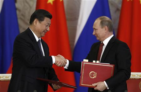 Russia's President Vladimir Putin (R) exchanges documents with his Chinese counterpart Xi Jinping during a signing ceremony at the Kremlin in Moscow March 22, 2013. REUTERS/Sergei Karpukhin