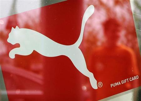 A man is reflected in a window with a Puma sign, at the factory outlet store in Herzogenaurach near Nuremberg April 10, 2007. REUTERS/Michaela Rehle