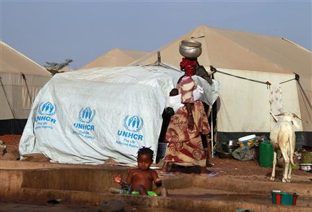 A woman walks past a child playing with water in a refugee camp in Sevare January 26, 2013. REUTERS/Eric Gaillard