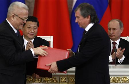 Russia's President Vladimir Putin (R, back) and his Chinese counterpart Xi Jinping (L, back) applaud while Rosneft President and Chairman of the Management Board Igor Sechin (R, front) exchanges documents with President of China National Petroleum Corporation (CNPC) and Vice Chairman and President of PetroChina Zhou Jiping during a signing ceremony at the Kremlin in Moscow March 22, 2013. REUTERS/Sergei Karpukhin