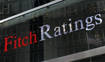 A flag is reflected on the window of the Fitch Ratings headquarters in New York February 6, 2013. REUTERS/Brendan McDermid