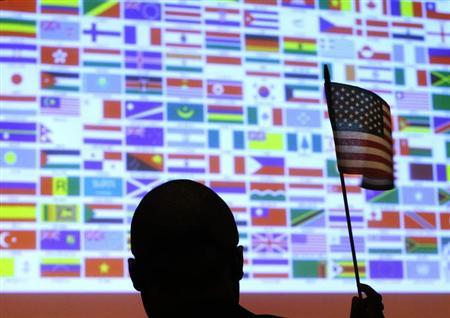 A new U.S. citizen waves a U.S. national flag in front of a display of flags of the more than 40 nations represented by the more than 90 immigrants becoming U.S. citizens during a naturalization ceremony at Boston College in Chestnut Hill, Massachusetts March 21, 2013. REUTERS/Brian Snyder