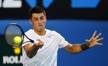 Bernard Tomic of Australia hits a return to Roger Federer of Switzerland during their men's singles match at the Australian Open tennis tournament in Melbourne January 19, 2013. REUTERS/Daniel Munoz/Files