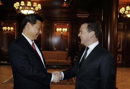 Russia's Prime Minister Dmitry Medvedev (R) and Chinese President Xi Jinping shake hands during their meeting at the Gorky residence, just outside Moscow March 23, 2013. REUTERS/Dmitry Astakhov/RIA Novosti/Pool