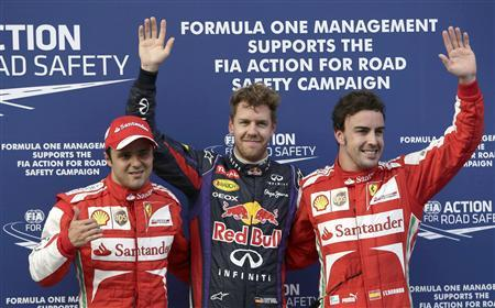 Red Bull Formula One driver Sebastian Vettel of Germany, flanked by Ferrari Formula One drivers Felipe Massa of Brazil (L) and Fernando Alonso of Spain, pose after the qualifying session for the Malaysian F1 Grand Prix at Sepang International Circuit outside Kuala Lumpur, March 23, 2013. REUTERS/Tim Chong