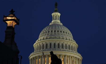 A man walks past the United States Capitol Dome before dawn in Washington March 22, 2013. REUTERS/Gary Cameron