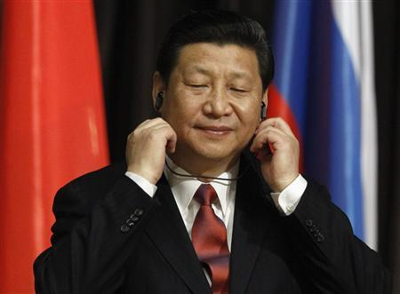 Chinese President Xi Jinping adjusts his earphones during his visit to the Moscow State Institute of International Relations in Moscow March 23, 2013. REUTERS/Sergei Karpukhin