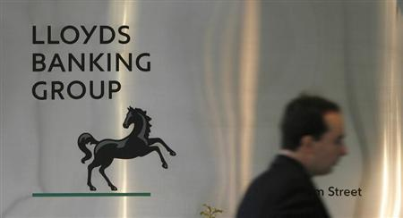 A man walks past a sign outside Lloyds Banking Group's headquarters in the City of London 27 February, 2009. REUTERS/Andrew Winning