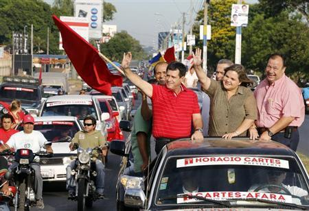 Presidential candidate Horacio Cartes of the Colorado Party (3rd R in red) waves to supporters in his motorcade during his visit to Luque March 12, 2013. REUTERS/Stringer