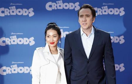Cast member Nicolas Cage and wife Alice Kim (L) arrive for the premiere of the film ''The Croods'' in New York, March 10, 2013. REUTERS/Carlo Allegri