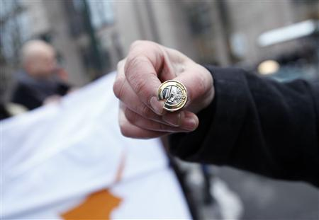 A man holds a broken 1-euro coin pin during a protest comprising of around 40 people from Cyprus, outside a Eurogroup meeting at the European Council building in Brussels March 24, 2013. REUTERS/Sebastien Pirlet