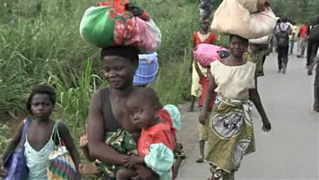 People walk as they leave Begoua for capital Bangui, 17 km (10 miles) away, in this still image taken from video, March 23, 2013. REUTERS/Reuters TV