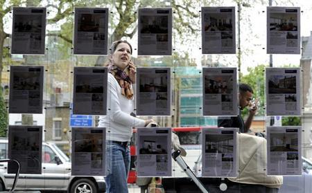 A woman stops to look in the window of an estate agent in Islington, north London April 29, 2010. REUTERS/Paul Hackett