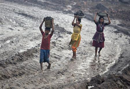 Locals carry coal from an open cast coal field at Dhanbad district in Jharkhand September 20, 2012. REUTERS/Ahmad Masood/Files
