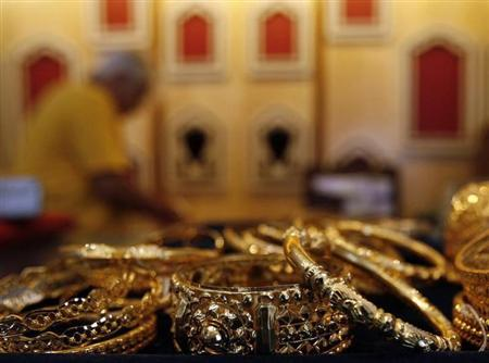 A gold jewellery shop owner arranges ornaments at a counter in Kolkata May 27, 2010. REUTERS/Parth Sanyal/Files