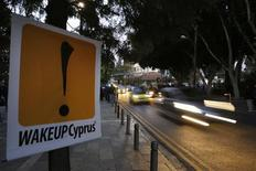 Машины едут мимо знака, установленного протестующими около парламента в Никосии, 24 марта 2013 года. Кипру удалось договориться с международными кредиторами о получении 10 миллиардов евро в обмен на закрытие второго крупнейшего банка страны. REUTERS/Yannis Behrakis (CYPRUS - Tags: BUSINESS POLITICS CIVIL UNREST)