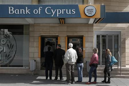 People queue up to make a transaction at an ATM outside a branch of Bank of Cyprus in Nicosia March 21, 2013. REUTERS/Yorgos Karahalis