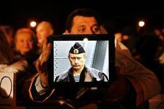 Россиянин, живущий на Кипре, держит в руках планшетник с изображением Владимира Путина на акции протеста у парламента в Никосии 22 марта 2013 года. Москва сигнализировала в понедельник, что может поддержать предложенную ЕС схему финансового спасения Кипра несмотря на гнев Кремля по поводу сделки, чреватой крупными убытками незастрахованных вкладчиков, включая многих россиян. REUTERS/Yannis Behrakis