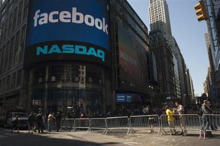Pedestrians walk near the NASDAQ Marketsite at the start of the listing for Facebook in New York May 18, 2012. REUTERS/Keith Bedford/Files
