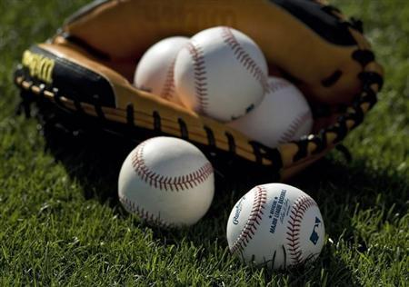 Baseballs and a catcher's mitt lie on the grass before a MLB spring training baseball game between the Boston Red Sox and Baltimore Orioles in Sarasota, Florida, March 25, 2013. REUTERS/Steve Nesius
