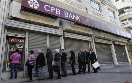 People queue up to make a transaction at an ATM machine outside a closed Cyprus Popular Bank (CPB) branch in Athens March 22, 2013. REUTERS/John Kolesidis