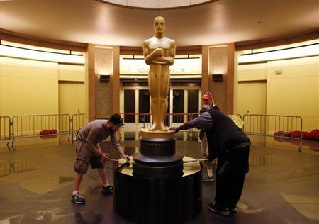 Production assistant Geoffrey Doleman (L) and props department head Frank Roach (R) use measuring tapes to center an Oscar statue on a pedestal in the lower rotunda outside the Kodak Theatre while head scenic artist Dena D'Angelo (rear R) looks on as preparations for the Oscars continue in Hollywood, California February 22, 2012. REUTERS/Danny Moloshok