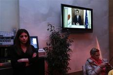 People sit at a cafeteria as Cyprus' President Nicos Anastasiades addresses the nation in Nicosia March 25, 2013. REUTERS/Yorgos Karahalis