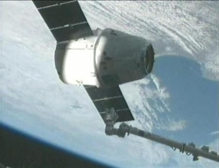 The SpaceX Dragon capsule is captured by the crew of the International Space Station using its robotic arm in this screen capture from NASA handout video released March 3, 2013. REUTERS/NASA/Handout