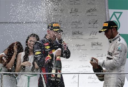 Third placed Mercedes Formula One driver Lewis Hamilton (R) of Britain sprays champagne at winner Red Bull Formula One driver Sebastian Vettel of Germany during the victory ceremony of the Malaysian F1 Grand Prix at Sepang International Circuit March 24, 2013. REUTERS/Tim Chong