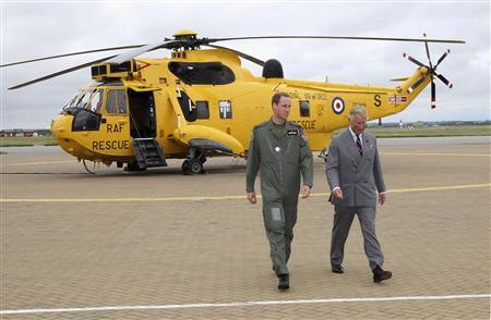 Britain's Prince Charles (R) and his son Prince William walk back to the Royal Air Force rescue base after Prince William showed his father around his Sea King helicopter at RAF Valley, in Valley, Wales in a July 9, 2012 file photo. REUTERS/Pool/Files