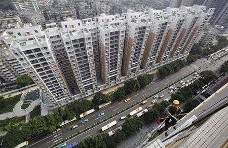 A worker cleans the exterior of a residential building in Guangzhou, Guangdong province August 28, 2010. REUTERS/Joe Tan/Files