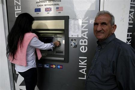 A man waits to make a transaction at a Laiki Bank ATM in Nicosia March 25, 2013. REUTERS/Yorgos Karahalis
