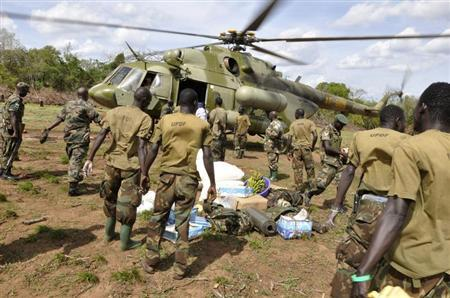 Ugandan soldiers, who are tracking down Lord's Resistance Army (LRA) fugitive leaders, load supplies off a military helicopter in a forest bordering Central African Republic (CAR), South Sudan and Democratic Republic of Congo, near river Chinko April 18, 2012. REUTERS/Stringer