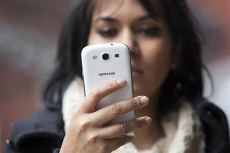 A woman uses a mobile phone in north London February 20, 2013. REUTERS/Neil Hall