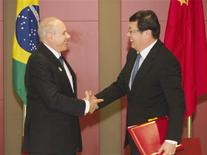 Le ministre des Finances brésilien Guido Mantega et son homologue chinois au sommet des Brics (Brésil, Russie, Inde, Chine, Afrique du Sud), à Durban. Chine et Brésil ont signé mardi un accord portant sur des échanges dans leurs devises respectives pour un montant d'environ 23 milliards d'euros par an, une démarche qui vise à réduire leur dépendance vis-à-vis du dollar américain. /Photo prise le 26 mars 2013/REUTERS/Rogan Ward