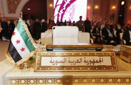 The Syrian opposition flag is seen in front of the seat of the Syrian delegation at the opening the Arab League summit in Doha March 26, 2013. REUTERS/Ahmed Jadallah