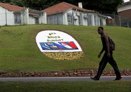 A man walks past a floral display announcing the 5th BRICS Summit in Durban, March 25, 2013. REUTERS/Rogan Ward