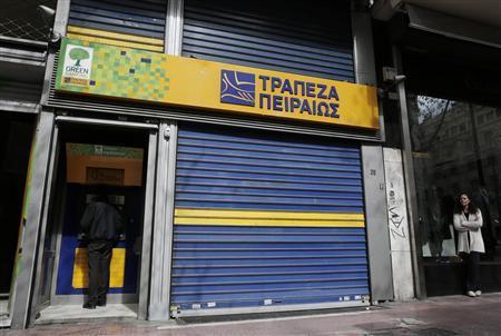 A man makes a transaction at an ATM machine outside a Piraeus bank branch in central Athens March 26, 2013. REUTERS/John Kolesidis